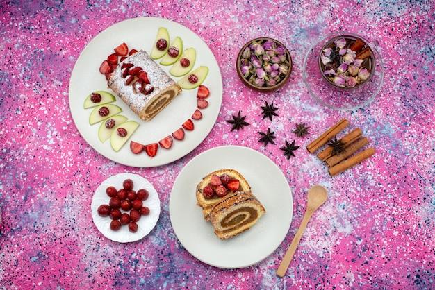 Torta di rotolo distante superiore all'interno del piatto con mele e fragole insieme a cannella e tè sulla frutta dolce del biscotto colorato della torta della scrivania