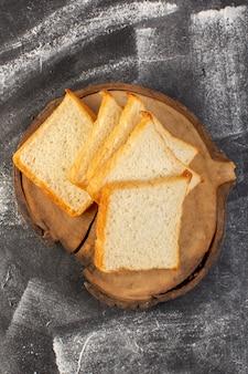 トップ遠景パンは茶色の木製の机と灰色の背景の生地のパンのパンに白パンをパンします。