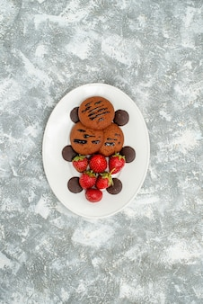 Top distant view chocolate cookies strawberries and round chocolates on the white oval plate on the grey-white ground