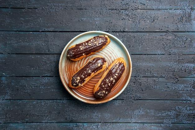 Вид сверху шоколадные эклеры на овальной тарелке на темном деревянном столе