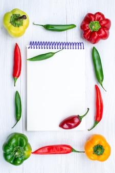 Peperoni colorati di vista in lontananza superiore allineati con il blocco note dei peperoni piccanti su bianco
