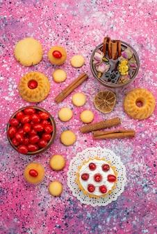 Верхний далекий вид кремовый торт со свежей красной клюквой вместе с печеньем с корицей и чаем на ярком столе, печенье, сладкие ягоды