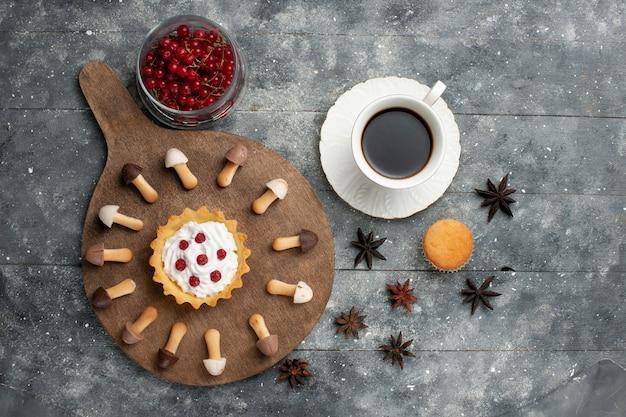 Tazza di caffè vista in lontananza superiore con torta biscotto e mirtilli rossi sul liquido biscotto scrivania grigia