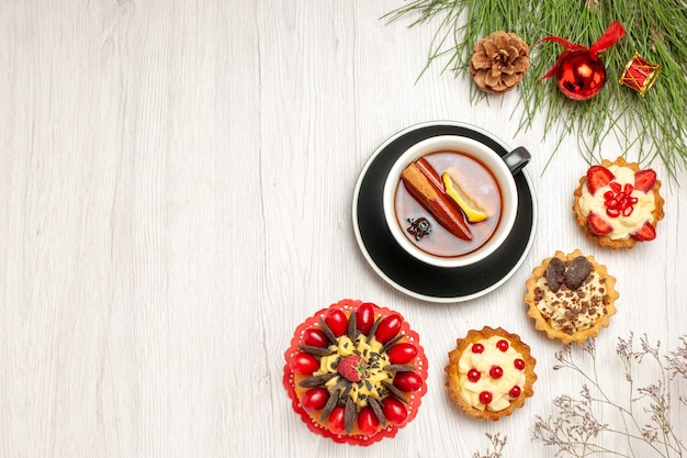 Top distant view a cup of lemon cinnamon tea berry cake tarts and the pine tree leaves with christmas toys at the right side of the white wooden ground