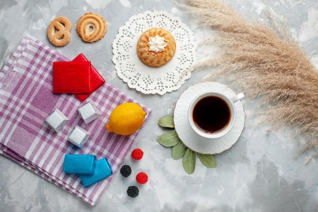 Top vista distante tazza di tè caldo all'interno della tazza bianca con cioccolatini al limone torta sulla luce