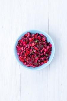 Insalata di barbabietola deliziosa vista dall'alto in lontananza affettata con verdure all'interno del piatto blu sullo scrittorio luminoso, insalata di salute del pasto di cibo di vitamina vegetale