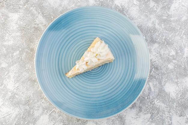 灰色の背景のビスケットケーキティー甘いクリームに青い丸皿の内側の遠景おいしいケーキスライス