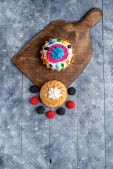 Deliziosa torta vista dall'alto in lontananza con panna e caramelle insieme a frutti di bosco sulla luce