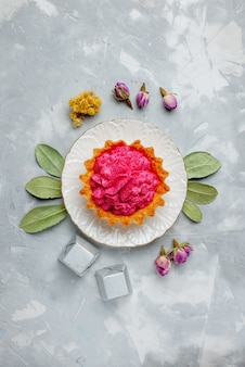 Top vista in lontananza deliziosa torta con crema rosa e cioccolatini sulla scrivania leggera, torta biscotto dolce cuocere lo zucchero alla crema