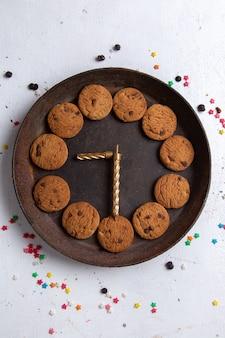 Biscotti al cioccolato deliziosi vista dall'alto in lontananza all'interno del piatto rotondo marrone sul tè dolce biscotto sfondo bianco