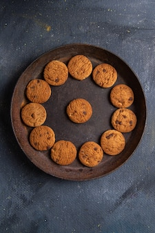 Top distant view delicious chocolate cookies inside dark round plate on the dark-grey background cookie biscuit sweet