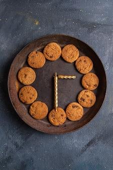 Вид сверху вкусное шоколадное печенье внутри темной круглой тарелки на темно-сером столе, печенье, печенье, сладкое