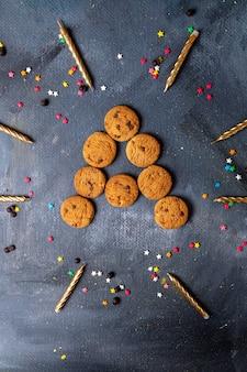 Сверху вдалеке вкусное шоколадное печенье со свечами и украшениями на темно-сером фоне печенье бисквит сладкий чай