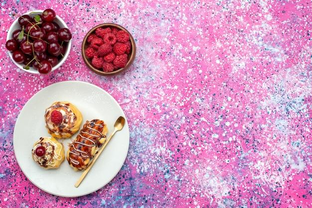 色付きの背景のケーキビスケットの甘い焼きたての新鮮な果物と一緒に白いプレートの中にクリームとチョコレートが入ったおいしい遠方のおいしいフルーツケーキ