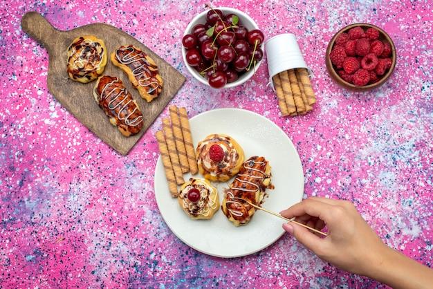 ピンクの床のビスケットの甘い焼きたての新鮮な果物と一緒に白いプレートの中にクリームとチョコレートが入ったおいしいフルーティーなケーキの遠景