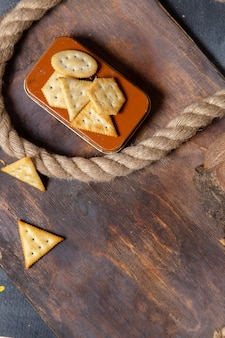 Top distant view different crackers salted with roeps on the wooden desk cracker crisp snack photo