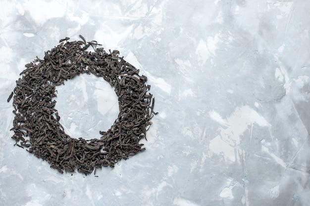 Vista in lontananza superiore tè essiccato di colore nero che forma un cerchio sul tavolo luminoso, colore secco del tè di grano
