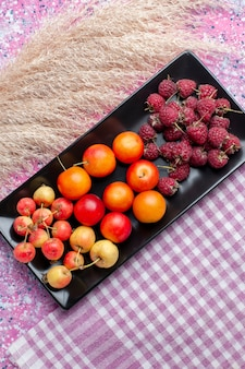 Top distant view of fresh fruits raspberries and plums inside black form on pink surface