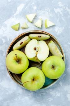 Vista in lontananza superiore mele verdi fresche affettate e frutti interi sulla superficie leggera frutta fresca e pastosa vitamina cibo maturo
