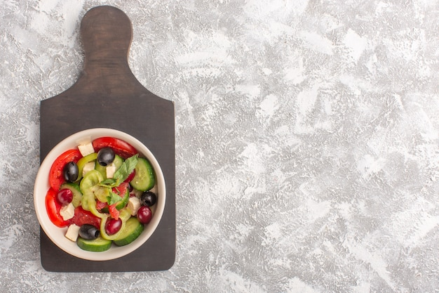 灰色の机の上のプレートの内側にスライスしたキュウリ、トマト、オリーブ、白チーズを添えた新鮮な野菜サラダのトップ遠景野菜料理サラダミール