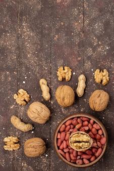 Вид сверху на свежие цельные ореховые грецкие орехи и фисташки, выложенные на коричневом ореховом орехе