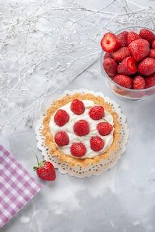 Vista dall'alto in lontananza piccola torta con panna e fragole rosse fresche su bianco, torta di frutta bacca biscotto crema cuocere