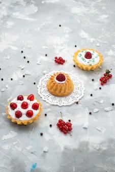 Top vista in lontananza piccole torte gustose con crema e frutti rossi sulla crema di zucchero biscotto dolce torta scrivania grigia