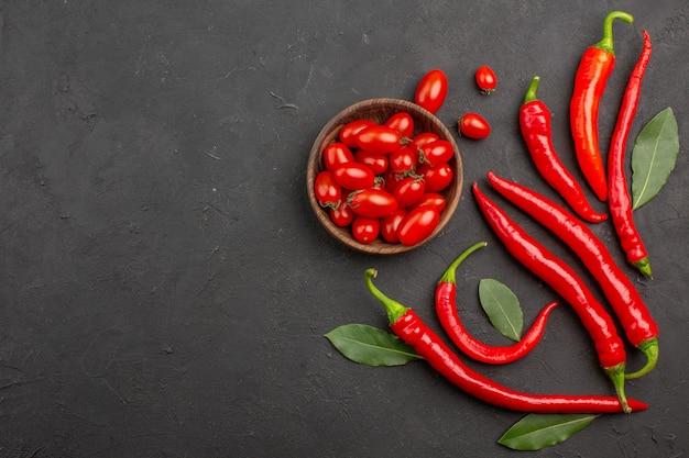 Peperoni rossi di vista in lontananza e foglie di paga e una ciotola di pomodorini sulla tavola nera