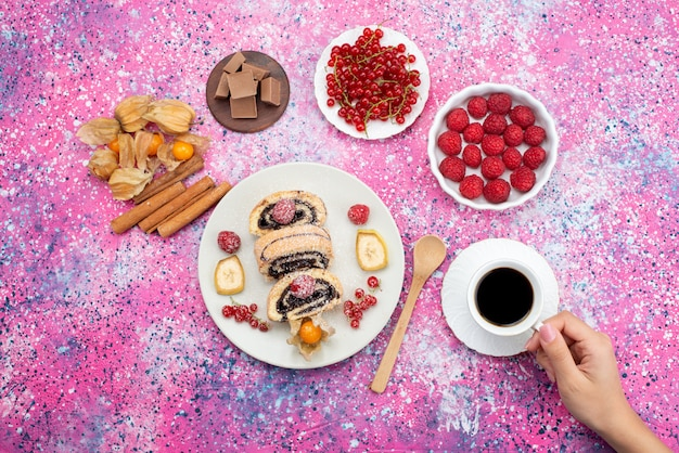 Top distant view roll cake inside plate with different fruits and cinnamon along with coffee on the colored desk cake biscuit sweet fruit