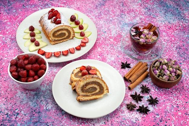 色付きのデスクケーキビスケット甘いフルーツの白いプレートシナモンティー内のさまざまなフルーツとトップ遠景ロールケーキスライス