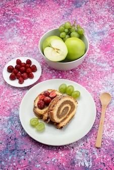 色付きのデスクケーキビスケット甘い果物の白いプレート内のさまざまな果物のトップ遠景ロールケーキスライス