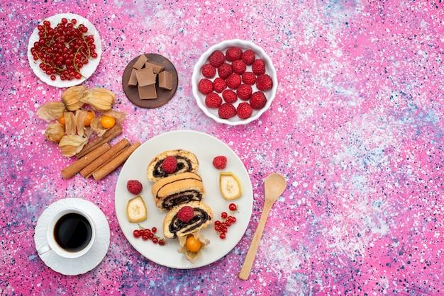 色とりどりのデスクケーキビスケット甘いフルーツのコーヒーとチョコのバーと白いプレート内のさまざまなフルーツとトップ遠景ロールケーキスライス
