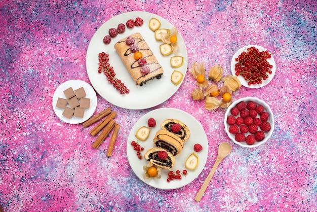 色付きの背景のケーキビスケット甘い色の白いプレート内の果物とトップ遠景ロールケーキ