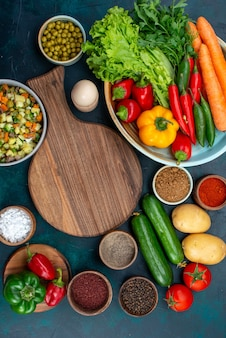 Vista in lontananza superiore insalata di verdure affettata condita con fette di pollo all'interno del piatto con verdure fresche sul cibo di verdure insalata pranzo spuntino scrivania blu