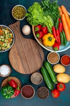 Вид сверху нарезанный овощной салат, приправленный кусочками курицы внутри тарелки со свежими овощами на синем столе, закуска, обед, салат, овощная еда