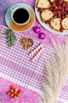 Vista in lontananza superiore affettato torte gustose con caffè e fragole rosse sulla torta rosa chiaro scrivania zucchero cuocere torta biscotto dolce