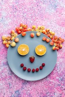 明るいピンクの机の上の皿の中の果物からのトップ遠景笑顔果物新鮮な熟したまろやかな色