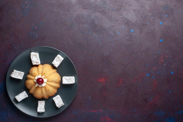 Верхний далекий вид сахарной пудры, вкусной нуги с тортом внутри тарелки на темной поверхности