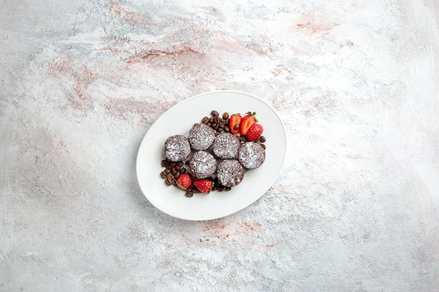 Top distant view tasty chocolate cakes with strawberries and chocolate chips on white surface biscuit cake bake sugar sweet pie cookie