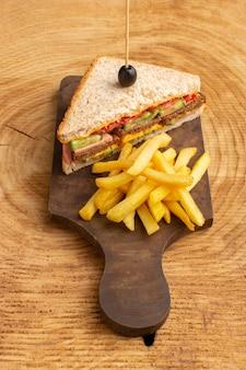 Вид сверху вкусный бутерброд с оливковой ветчиной, помидорами, овощами и картофелем фри на деревянном фоне сэндвич еда закуска фото завтрак