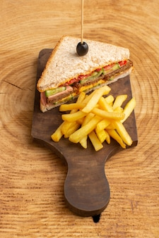 Top distant view tasty sandwich with olive ham tomatoes vegetables along with french fries on the wooden background sandwich food snack breakfast photo