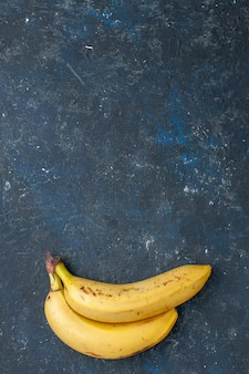 Top distant view yellow bananas pair of berries on dark desk, fruit berry fresh mellow food health vitamine sweet