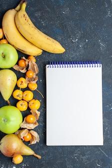 Vista in lontananza le banane gialle coppia di bacche con mele verdi fresche pere e ciliegie dolci blocco note sulla scrivania blu scuro, vitamina bacca