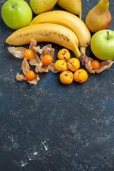 Вид сверху желтые бананы, пара ягод с зелеными яблоками, груши на темно-синей, фруктовой ягоде, свежей, витаминной, сладкой мякоти