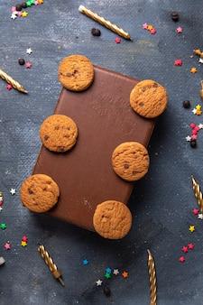 Сверху вдалеке вкусное шоколадное печенье на коричневом футляре с чаем и свечами на темном фоне печенье бисквит сладкий чай