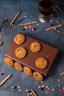 Сверху вдалеке вкусное шоколадное печенье на коричневом футляре с чайными свечами на темно-сером фоне печенье бисквит сладкий чай