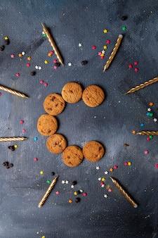 Сверху вдаль вкусное шоколадное печенье со свечами и декором на темно-сером фоне печенье бисквит сладкий чай сахар