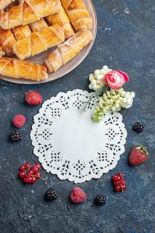 Вид сверху на вкусные сладкие браслеты с начинкой внутри тарелки со свежими ягодами на темном столе, сладкое бисквитное печенье, выпечка