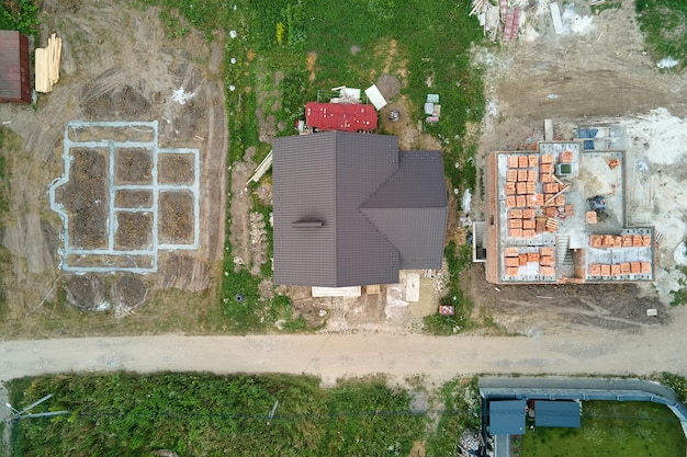 Top down aerial view of building works of new house concrete foundation on construction site.