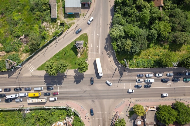 Top down aerial view of busy street intersection with moving cars traffic.